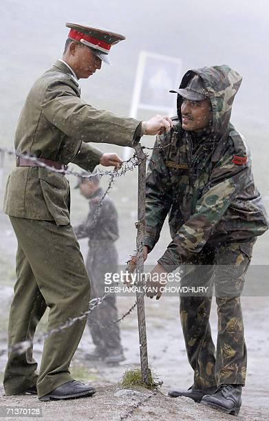 Chinese and an Indian soldiers put back in position a barbed wire fence following a meeting of military representatives of the two countries at their...