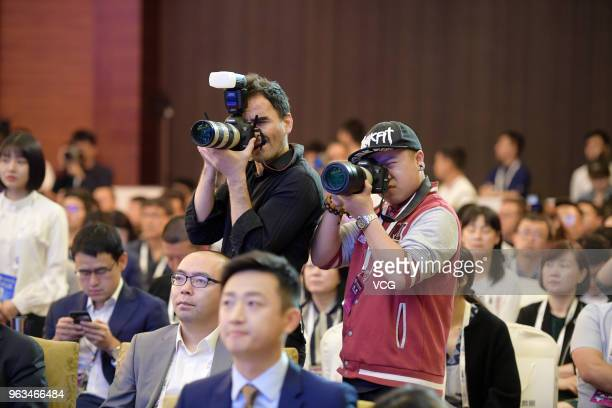 Chinese and foreign journalists take photos at 'Exploring the New Digital Ecosystem' session during the China International Big Data Industry Expo...