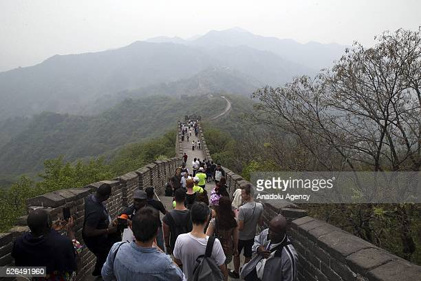 Chinese and foreign tourists walk on a section of the Great Wall of China in Beijing China on April 30 2016