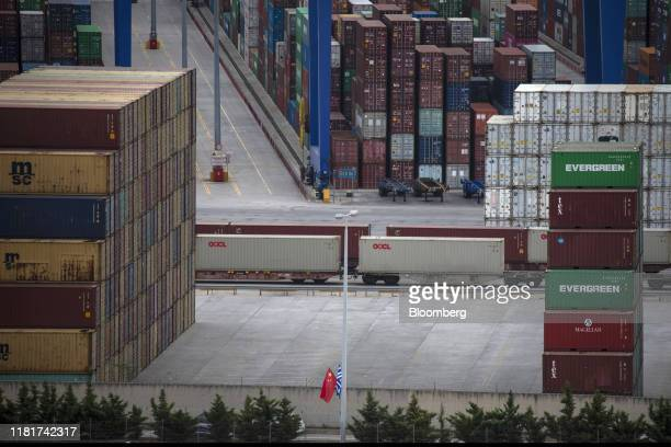 Chinese and Greek flags sit by shipping containers and rail wagons at the China Ocean Shipping Co. Ltd. Container terminal operations at Piraeus...