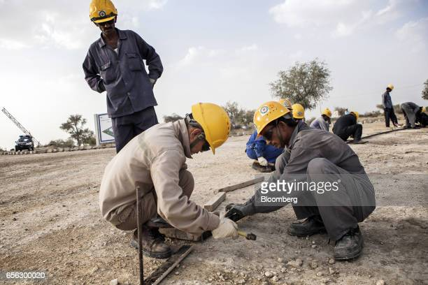 Chinese and Pakistani workers labor at the construction site for an access road at the Sindh Engro Coal Mining Co site in the Thar desert Pakistan on...