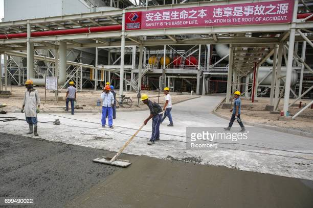 Chinese and Pakistani workers labor on the construction of a road beneath a banner bearing a safety message written in Mandarin Chinese script and...