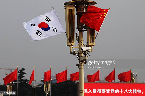 Chinese and South Korean flags flutter in front of Tiananmen Rostrum on June 27 2013 in Beijing China South Korean President Park GeunHye is on a...