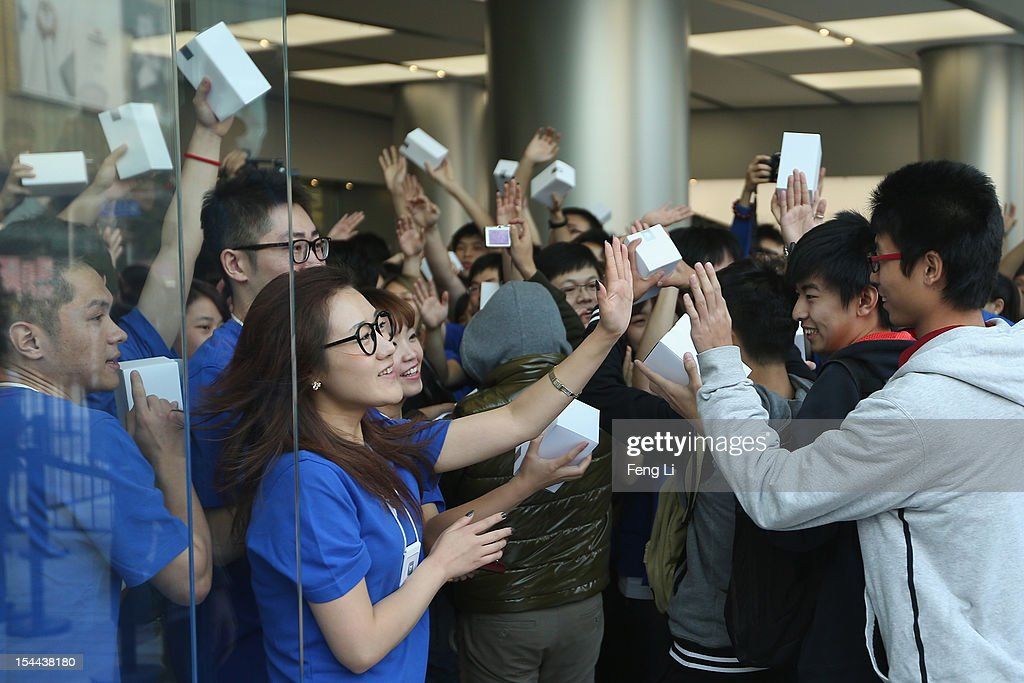 Chinese Apple staff members greet customers as they enter the new Apple Store in Wangfujing shopping district on October 20, 2012 in Beijing, China. Apple Inc. opened its sixth retail store on the Chinese mainland Saturday. The new Wangfujing store is Apple's largest retail store in Asia.