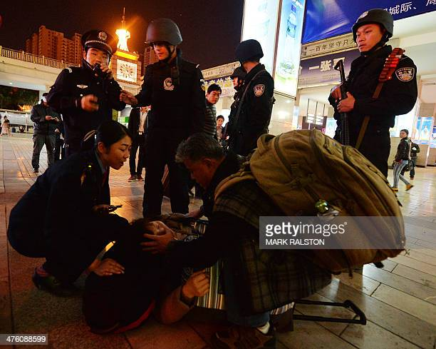 Chinese armed police and officials help a sick woman at the scene of the terror attack at the main train station in Kunming, Yunnan Province on March...