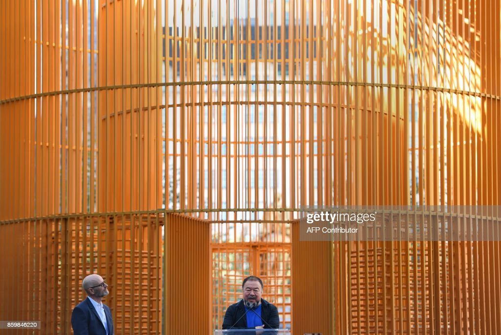 Chinese Artist Ai Weiwei (C) attends his art installation exploring migration entitled 'Good Fences Make Good Neighbors' during a press conference at Doris C. Freedman Plaza in Central Park, New York City, on October 10, 2017 ahead of October 12's public opening of his multi-venue exhibition inspired by the international migration crisis. Spread across multiple New York boroughs, the multi-site project transforms metal wire security fences into artistic symbols by installing them in varying, site-specific forms at locations across the city. /