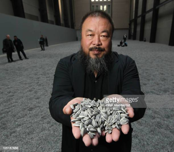 Chinese Artist Ai Weiwei holds some seeds from his Unilever Installation 'Sunflower Seeds' at The Tate Modern on October 11 2010 in London England...