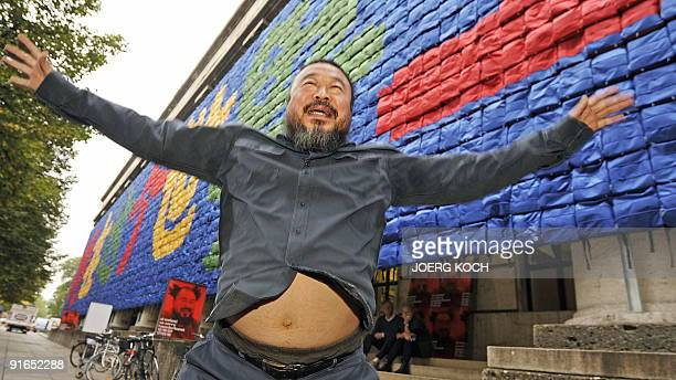 Chinese artist Ai Weiwei jumps in the air in front of his installation called 'Remembering' at the 'Haus der Kunst' ahead of the exhibition 'So...