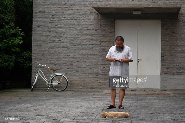 Chinese artist Ai Weiwei photographs a cat inside his home on the day of his court hearing in Beijing on July 20 2012 Ai is unlikely to win a...