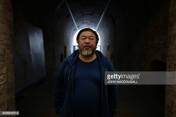 Chinese artist Ai Weiwei poses in his studio in Berlin on February 21 2017 / AFP / John MACDOUGALL