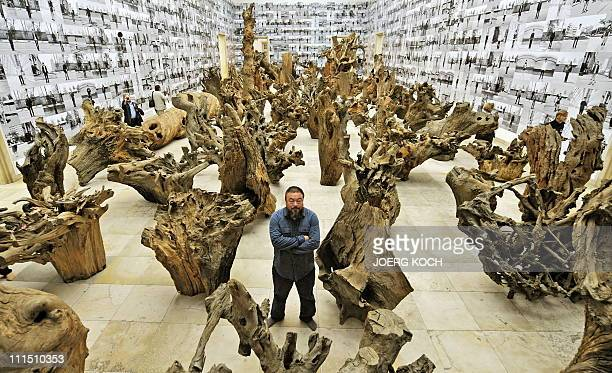 Chinese artist Ai Weiwei poses in the middle of his work made of 100 pieces of trees and called Rooted Upon at the Haus der Kunst during the...