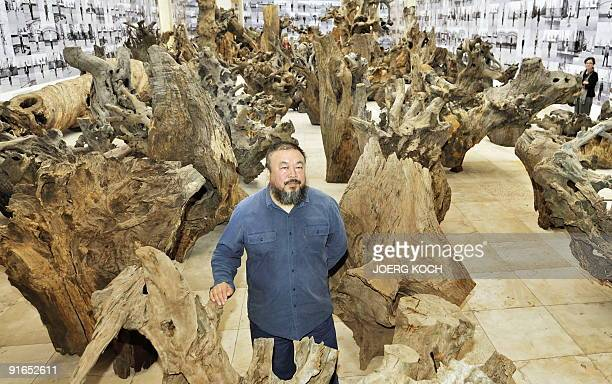 Chinese artist Ai Weiwei poses in the middle of his work made of 100 pieces of trees and called 'Rooted Upon' at the 'Haus der Kunst' during the...
