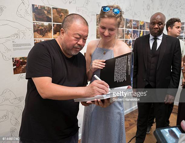 Chinese artist Ai Weiwei signs a book for a fan at the opening of FOAM #SafePassage Amsterdam Netherlands 15th September 2016