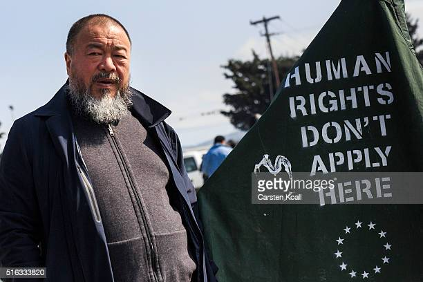 Chinese artist Ai Weiwei stands beside a banner with the slogan 'Human Rights Don't Apply Here' in the Idomeni refugee camp at the Greek Macedonia...