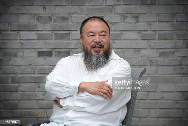 Chinese artist Ai Weiwei waits at his home after claiming he was barred from attending his court hearing against a multimilliondollar tax fine in...