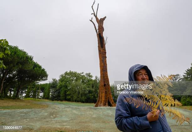 """Chinese artist and dissident activist Ai Weiwei holds a fern while standing in front """"Pequi Tree"""" , a 32 meters sculpture molded from a 1200 years..."""
