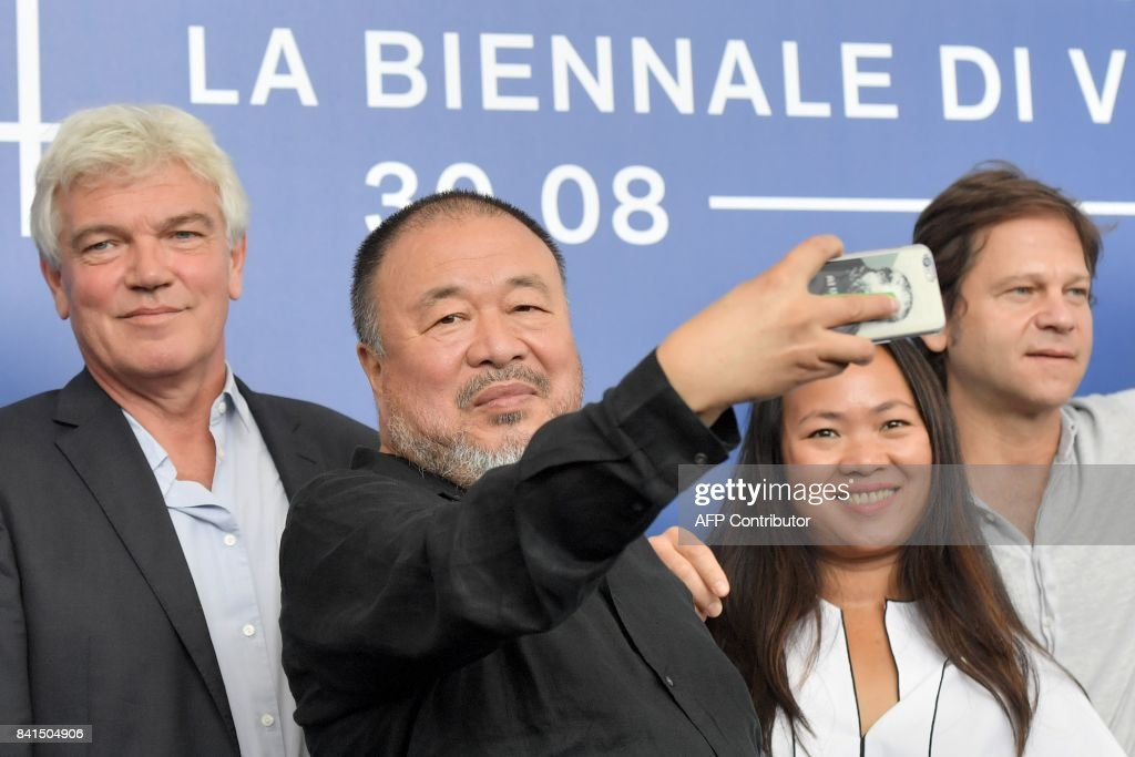 Chinese artist and producer Ai Weiwei (C) attends the photocall of the movie 'Human Flow' presented in competition at the 74th Venice Film Festival on September 1, 2017 at Venice Lido. / AFP PHOTO / Tiziana FABI