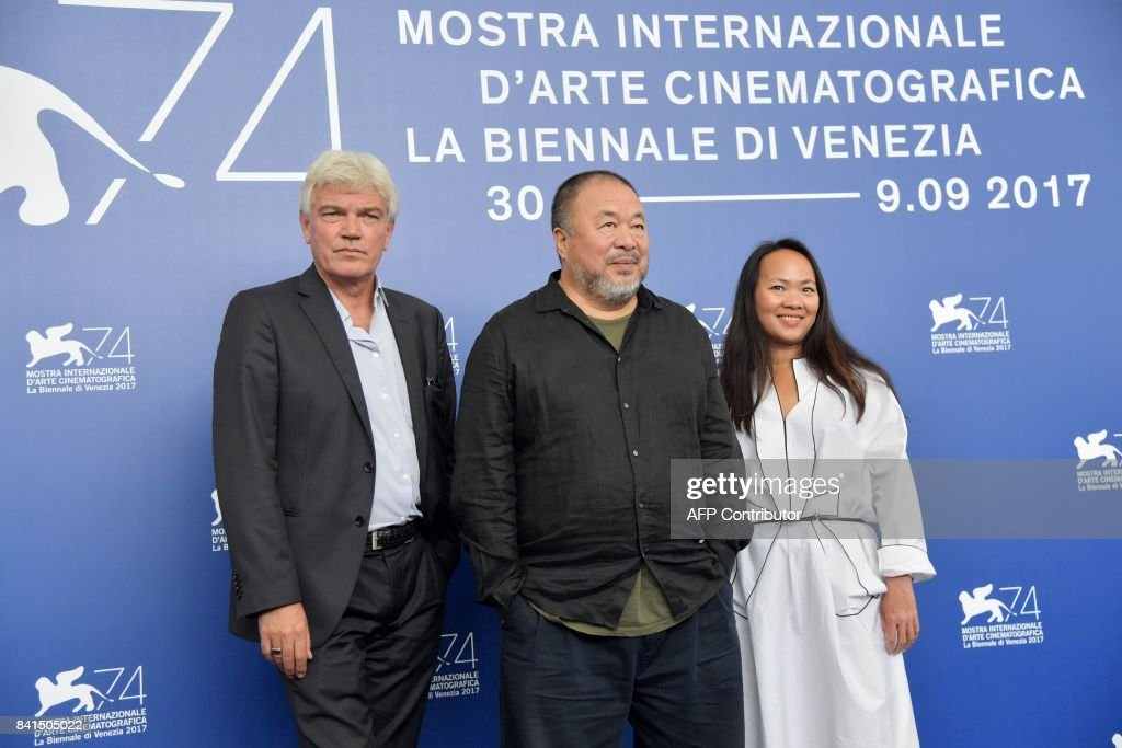 Chinese artist and producer Ai Weiwei (C), producers Chin-Chin Yap and Heino Deckert (L) attend the photocall of the movie 'Human Flow' presented in competition at the 74th Venice Film Festival on September 1, 2017 at Venice Lido. / AFP PHOTO / Tiziana FABI