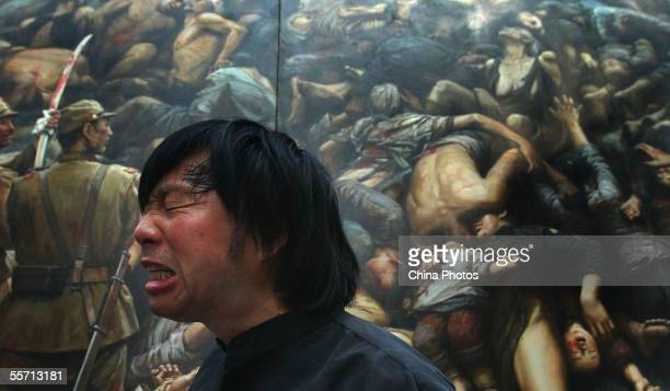 Chinese artist Li Zijian condemns the atrocity of Japanese troops in front of his canvas work Nanjing Massacre shown at the Memorial For Nanjing...