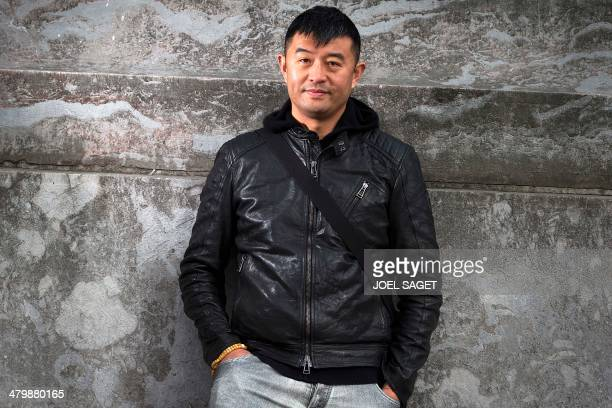 Chinese artist Liu Bolin poses before the installation of his art creation a giant fist sculpture 'Iron First' at the Grand Palais museum in Paris on...