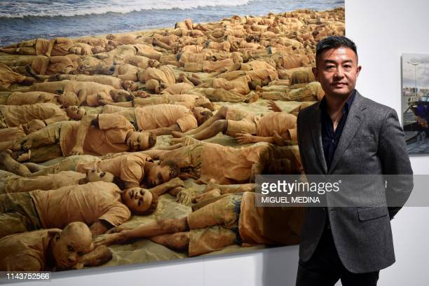 Chinese artist Liu Bolin poses next to one of his artwork entitled 'Memory Day 2015' from the series 'Migrants' during his exhibition 'Visible...