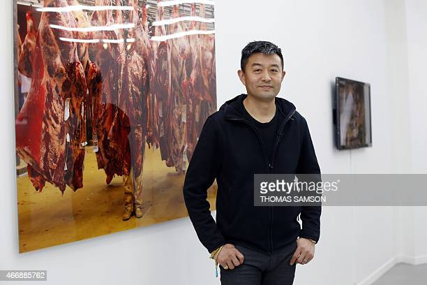 Chinese artist Liu Bolin poses on March 19 2015 in Paris in front of his work CAPTION