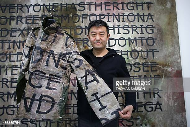 Chinese artist Liu Bolin poses on March 19 2015 in Paris with a jacket he wore during a performance with French conceptual artist Alexis Rero CAPTION