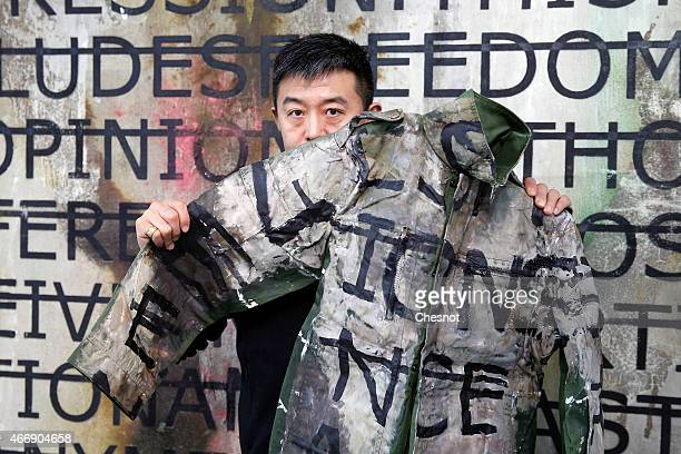 Chinese artist Liu Bolin poses with a jacket he wore during a performance on March 19 2015 in Paris France Liu Bolin is Internationally known and...