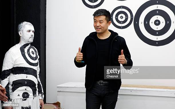 Chinese artist Liu Bolin poses with his last artwork at the galerie ParisBeijing on March 19 2015 in Paris France Liu Bolin is Internationally known...