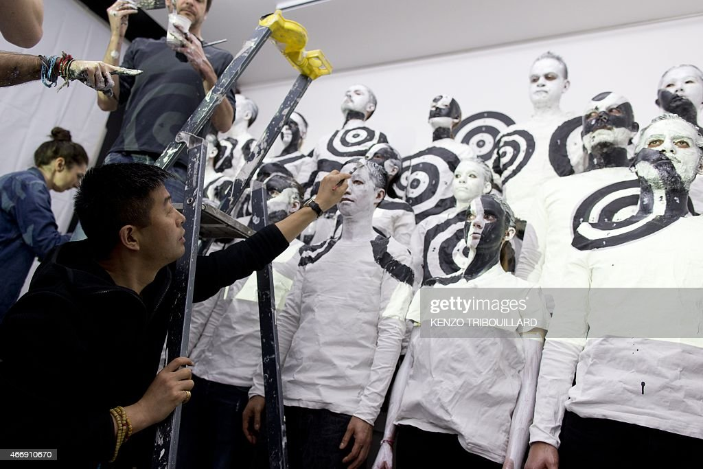 Chinese artist Liu Bolin takes part in a performance on March 19, 2015 in Paris.