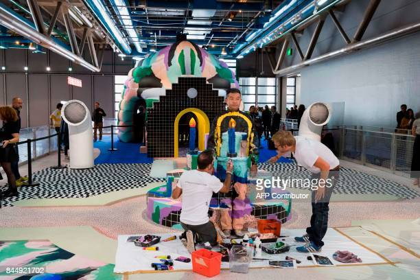Chinese artist Liu Bolin takes part in a performance with a 'Galerie Party' set created by designers Gaelle Gabillet et Stephane Villard during an...