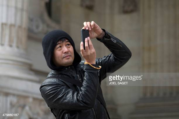 Chinese artist Liu Bolin takes pictures with a mobile phone during the installation of his art creation a giant fist sculpture 'Iron First' at the...