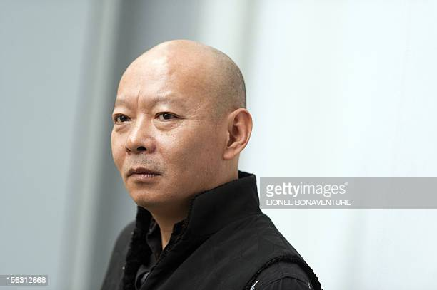 Chinese artist Yue Minjun poses as part of his exhibition entitled 'L'ombre d'un fou rire' on November 13 2012 at the Fondation Cartier building in...