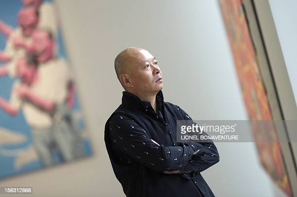 Chinese artist Yue Minjun poses in front of one of his paintings displayed in an exhibition devoted to his work and entitled 'L'ombre d'un fou rire'...