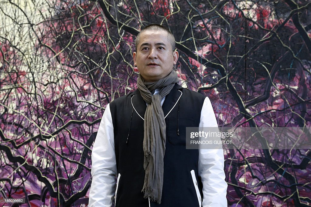 Chinese artist Zeng Fanzhi poses in front of one of his paintings, on October 17, 2013 at the Museum for Modern Art in Paris, ahead of the first restrospective of his work in France.