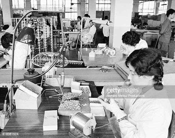 Chinese assembly line workers assemble television components at a factory in Shanghai.