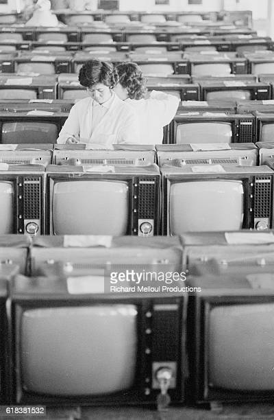 Chinese assembly line workers assemble TVs at a factory in Shanghai
