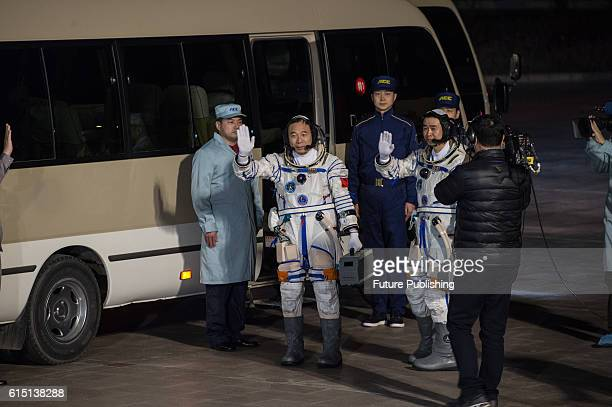 Chinese astronauts Jing Haipeng 2nd left and Chen Dong 2nd right bid farewell to the crowd before getting on Shenzhou11 spaceship at Jiuquan...