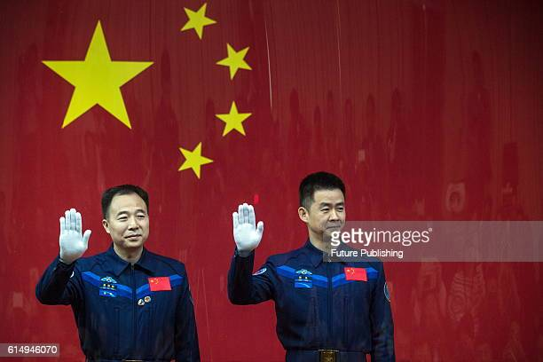 Chinese astronauts Jing Haipeng and Chen Dong after the glass wall attend a presser at the Jiuquan Satellite Launch Center on October 16 2016 in...