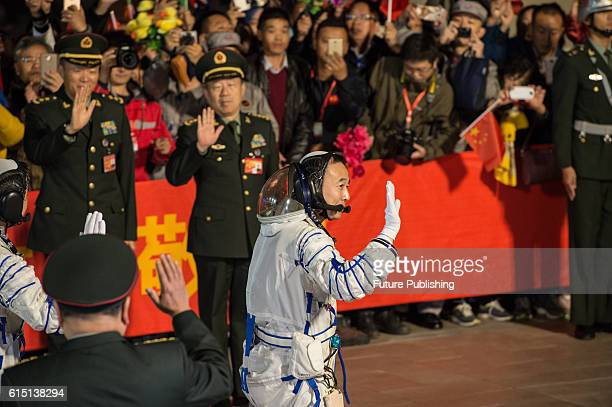 Chinese astronauts Jing Haipeng bids farewell to the crowd before getting on Shenzhou11 spaceship at Jiuquan Satellite Launch Center on October 17...