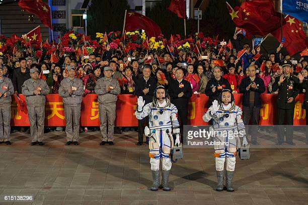Chinese astronauts Jing Haipeng right and Chen Dong left bid farewell to the crowd before getting on Shenzhou11 spaceship at Jiuquan Satellite Launch...