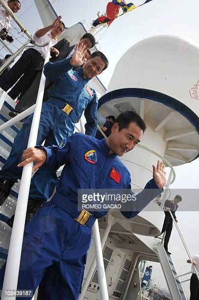 Chinese astronauts Zhai Zhigang and Nie Haisheng descend from the deck of the Chinese satellite monitoring ship MV Yuanwang5 on arrival at the...