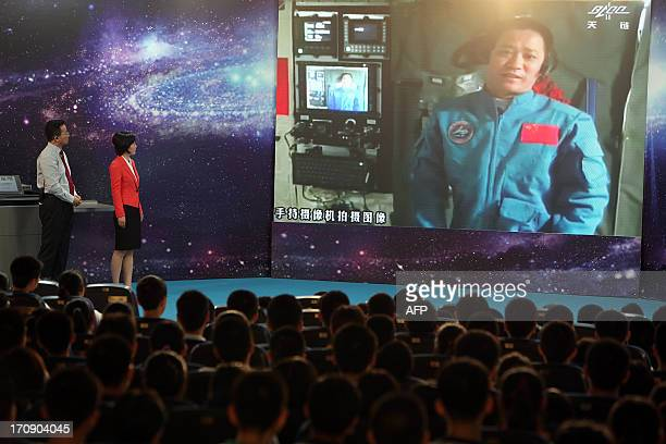 Chinese astrounaut mission commander Nie Haisheng speaks to students gathered in a school in Beijing as Chinese female astrounaut Wang Yaping gives...