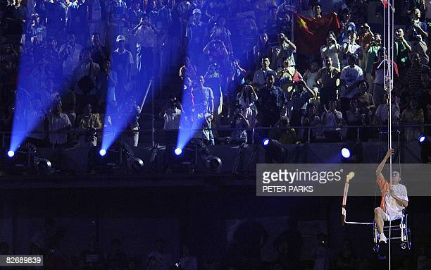 Chinese athlete Hou Bin winches himself up as he carries the torch in the National Stadium at the opening ceremony for the 2008 Beijing Paralympic...