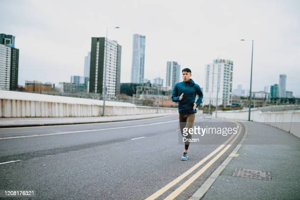 chinese athlete jogging on cloudy day outdoors - running stock pictures, royalty-free photos & images