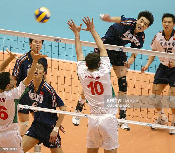 Chinese attacker An Jiajie spikes the ball over Algerian defenders Med Mehdi Hachemi Nabil Sahi during their match of the men's volleyball Asian and...