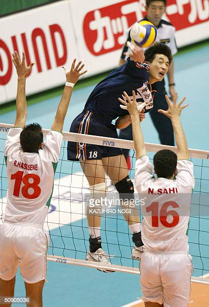 Chinese attacker An Jiajie spikes the ball over Algerian defenders Rafik Hassissene and Nabi Sahi during their match at the men's volleyball Asian...