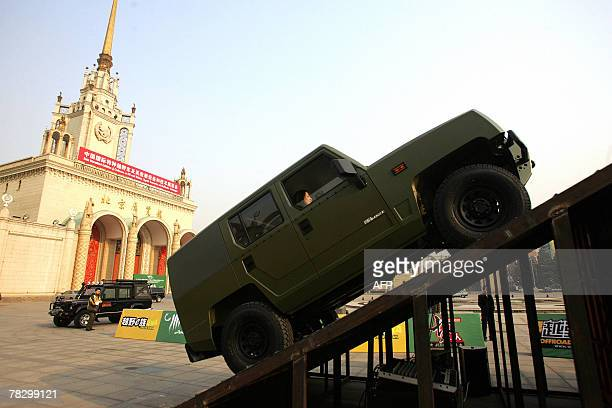 Chinese auto enthusiast admires a specially modified off-road vehicle on display at an exhibition in Beijing, 06 December 2007. Sales of passenger...