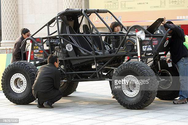 Chinese auto enthusiasts admire a specially modified off-road vehicle on display at an exhibition in Beijing, 06 December 2007. Sales of passenger...