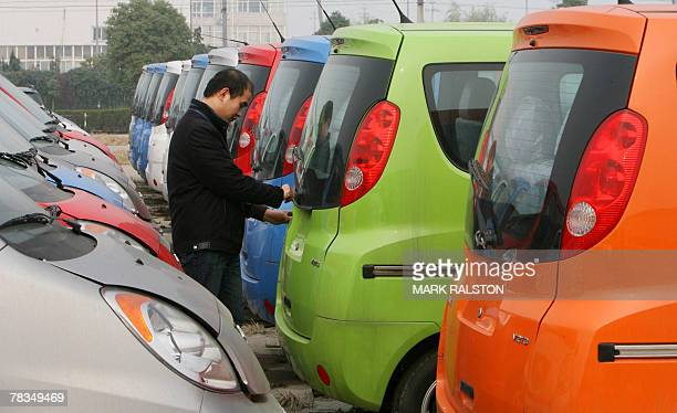 Chinese automotive worker checks Chery vehicles in the delivery yard of their factory in Wuhu, Anhui Province, 07 December 2007. The company may...